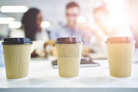 Craft paper cup of coffee to go with coworkers on background