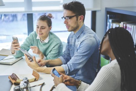 Group of students using modern device in library