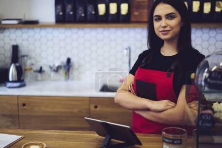 Professional female barista waiting for order to make aroma coffee for client standing near modern equipment