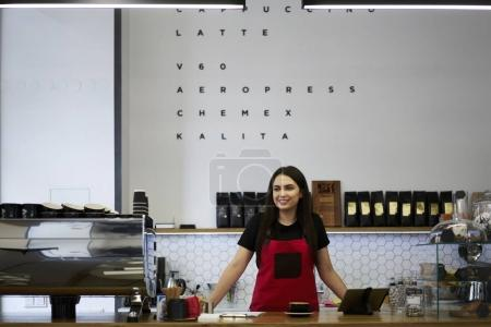 Charming female barista enjoying working process in coffee shop with equipment