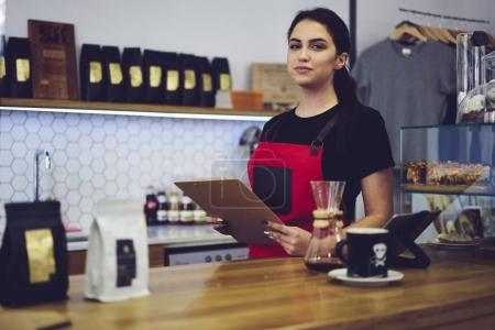 Experienced female barista preparing for revision in coffee shop