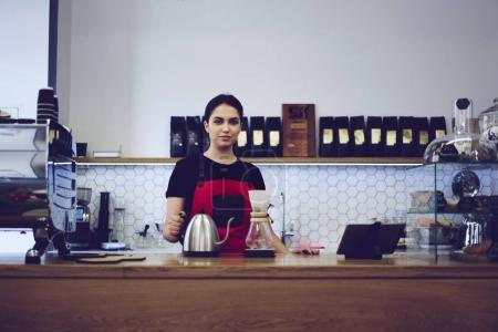 Young female barista making filtered coffee drink using special technology