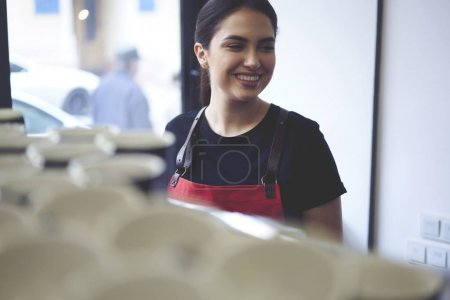 Woman server with smile standing in cafe interior