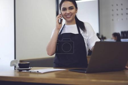 Photo for Cheerful attractive waitress having phone conversation with boss talking about working day income while making financial report using laptop - Royalty Free Image