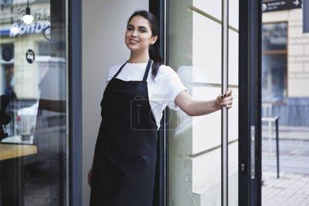 Woman entrepreneur barista standing at restaurant entrance