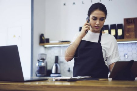 Woman coffee shop owner making finance accounting standing at bar with modern laptop and digital tablet
