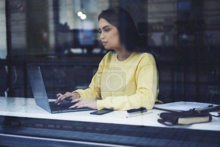 Business woman making remote job checking financial documentation via laptop computer