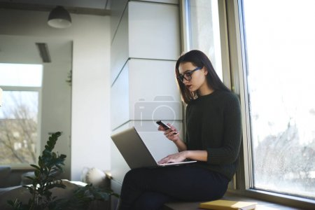 Beautiful hipster girl using laptop and 4G wireless internet connection for blogging
