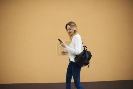 Hipster girl receiving funny sms message from friends on digital cellular using free 4G internet connection