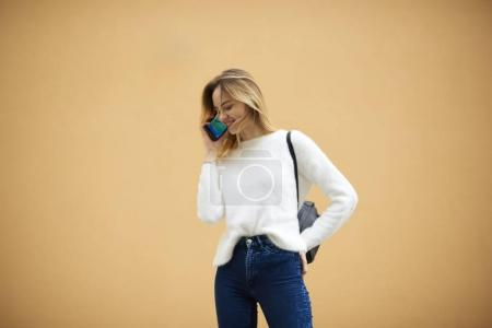 Smiling stylishly dressed young hipster in casual clothes talking with friends on modern mobile phone