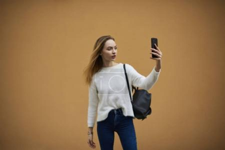Hipster girl making video call against background