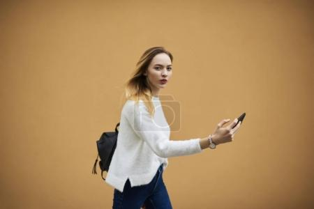 Hipster girl standing on colourful background with modern cellphone