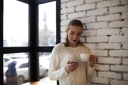 Hipster girl reading news standing near brick wall