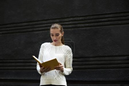 Concentrated charming hipster girl studying on reading interesting book outdoors while enjoying good day