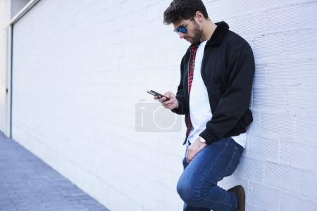 Hipster guy standing near copy space using cellular