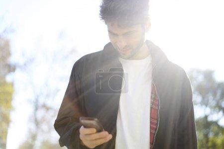 Photo pour Homme élégant naviguant sur Internet via smartphone debout sur la rue dans la journée ensoleillée - image libre de droit