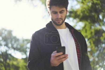 Photo pour Attrayant jeune voyageur masculin à la recherche d'informations sur des endroits intéressants en ville et de lire des informations sur le téléphone mobile - image libre de droit