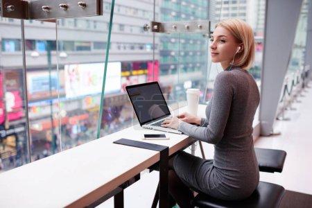 Photo pour Fille séduisante jeune hipster travailler pause café appréciant la chanson préférée de playlist via smartphone et écouteurs - image libre de droit