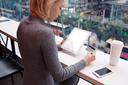 Young female using modern touchpad with mock up screen connected to 4G internet in coffee shop