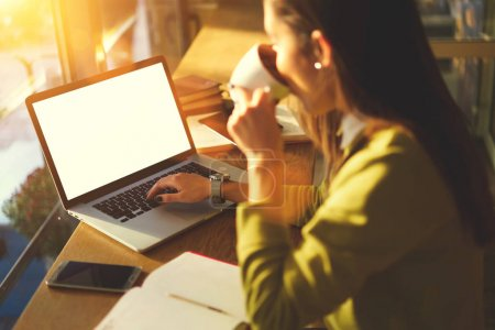 Female freelancer searching and analyzing information from web spending time in cafe indoors using technology