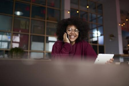 Young female using modern touchpad surfing internet chatting in social networks