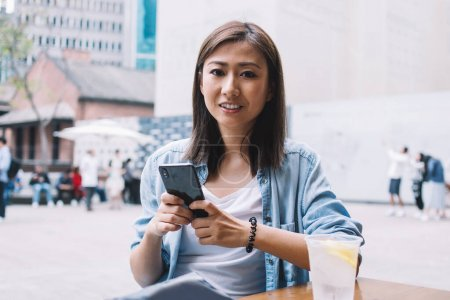 Photo for Portrait of pretty prosperous Asian female blogger with cute smile on face sending funny messages to friends via smartphone, young gorgeous woman enjoy recreation on leisure at city street - Royalty Free Image