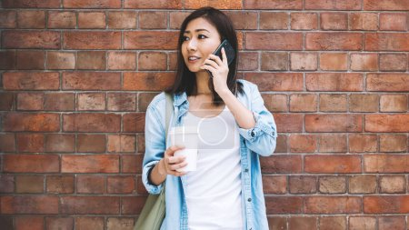 Photo for Young female person talking on mobile standing on urban brick wall background, attractive Chinese hipster girl having cellphone conversation in roaming near copy space for advertising text - Royalty Free Image