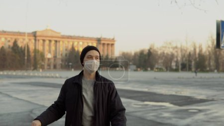 Photo for Guy stay in medical mask on empty city area, portrait - Royalty Free Image
