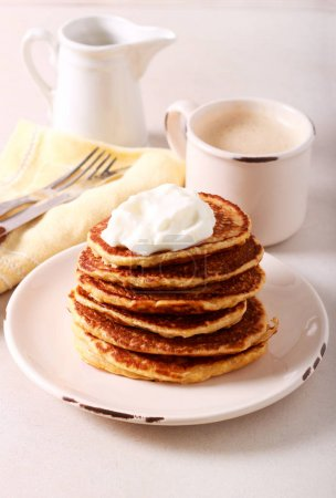 Photo for Pancakes heap with yogurt on top - Royalty Free Image