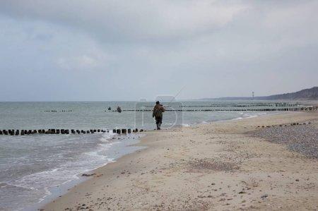 Photo pour Pêcheur marchant sur la plage baltique Curonian Spit - image libre de droit