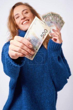 freudige Frau teilt Geld Griwna hält sie in den Händen auf einem gr
