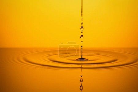 Photo pour Ondulation de la surface dorée du liquide jaune avec des gouttes - image libre de droit