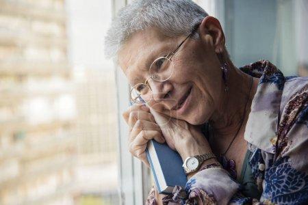 Photo pour Femme âgée tenant son livre préféré, se souvenant du vieil amour - image libre de droit