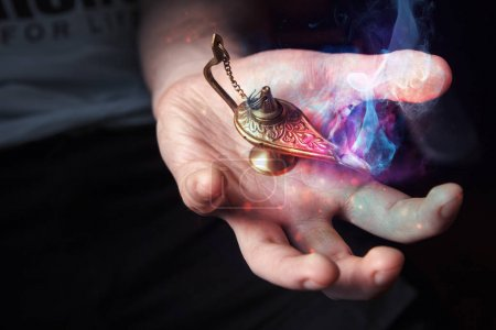 Photo for Young mans hand holding a magical, Aladdins lamp, fantasy smoke coming out - Royalty Free Image