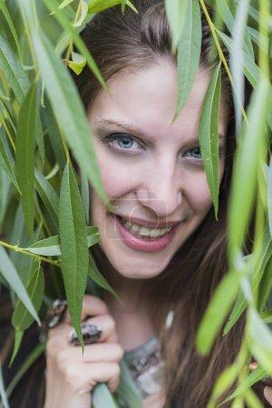 Heureuse femme gaie couverte de feuilles de lierre