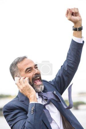Photo pour Cheering victorieux homme d'affaires senior recevant de bonnes nouvelles sur son téléphone portable - image libre de droit
