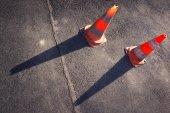 Two orange road cones on the gray asphalt