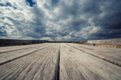 Wooden table outdoors under a dramatic sky