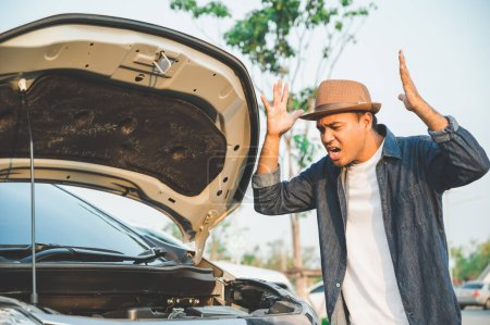 Młody azjatycki turysta prowadził samochód i zepsuł się po drodze. Przyszedł zobaczyć maskę samochodu..