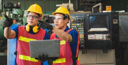 Photo pour Des travailleurs industriels asiatiques discutent de projets de construction d'ordinateurs portables dans de grandes installations industrielles. - image libre de droit