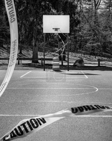 Photo for An outdoor basketball court stands closed to COVID-19 (Coronavirus). The basket is roped off by bright yellow caution tape and a pilon. From the view of the oposing basket caution tape is clearly readable in the forground. - Royalty Free Image