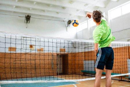 Photo pour Le gars s'est levé pour frapper la balle de volley. Il joue au volley-ball au gymnase. Le volley. Boule. Filet de volley . - image libre de droit