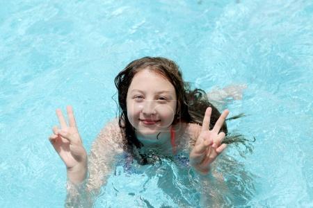 Photo pour Belle jeune fille de 13 ans montrant deux pouces vers le haut de nage dans la piscine au spa - image libre de droit