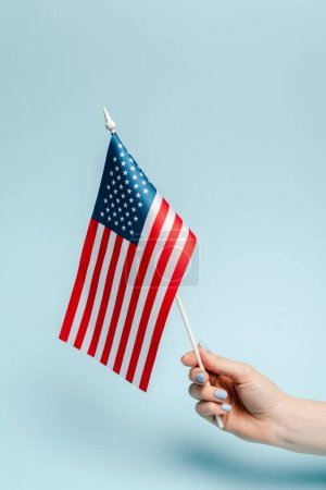 Photo pour Cropping view of woman holding american flag on blue background, coronavirus concept - image libre de droit