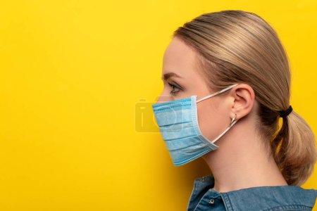 Photo pour Vue latérale de la jeune femme en masque médical sur fond jaune, concept de coronavirus - image libre de droit