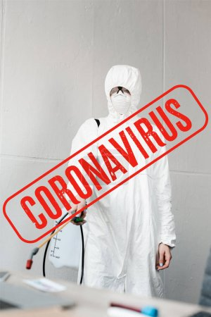 Photo for Selective focus of person in white hazmat suit, respirator and goggles disinfecting workplace in office, coronavirus illustration - Royalty Free Image