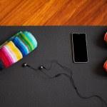 Sports mat with mobile phone, headphones, orange s...