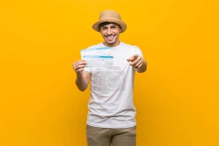 Photo pour Jeune homme hispanique tenant un billet d'avion sourire joyeux pointant vers l'avant . - image libre de droit