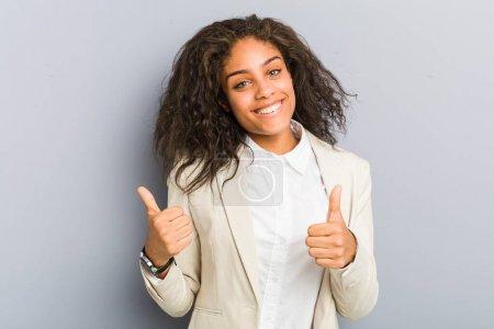 Photo pour Jeune femme d'affaires afro-américaine levant les pouces, souriante et confiante . - image libre de droit