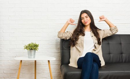 Young arab woman sitting on the sofa feels proud and self confident, example to follow.